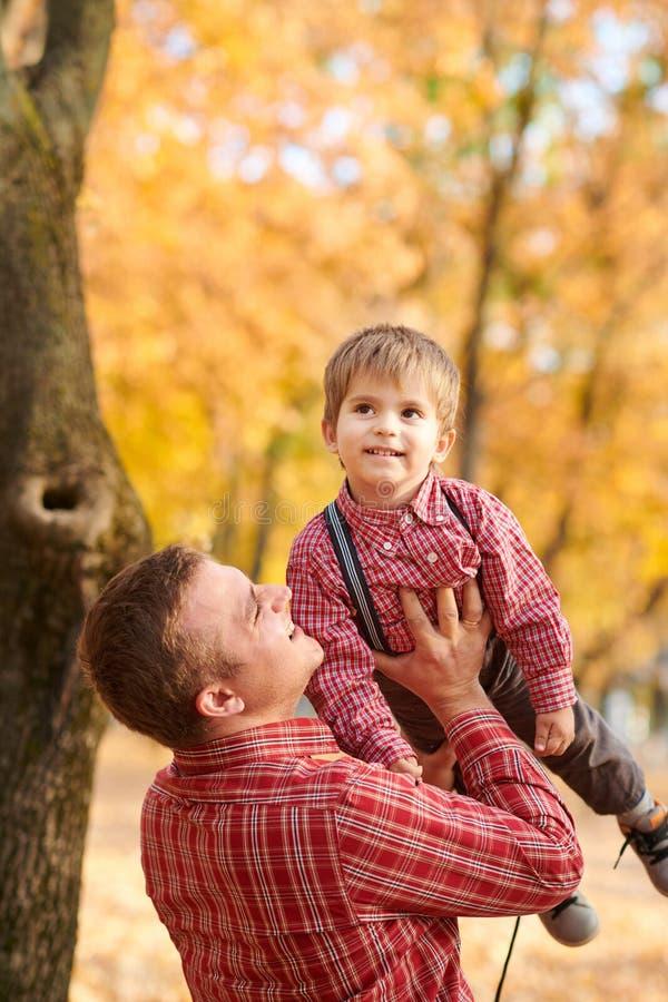 De vader werpt omhoog de jongenshoogte De vader en de zoon spelen en hebben pret in het park van de de herfststad Zij die, het gl stock afbeeldingen