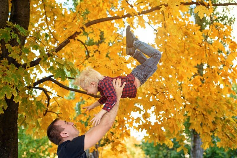 De vader werpt op zijn blonde zoon Gele bladeren op achtergrond Het concept van de familie royalty-vrije stock afbeeldingen