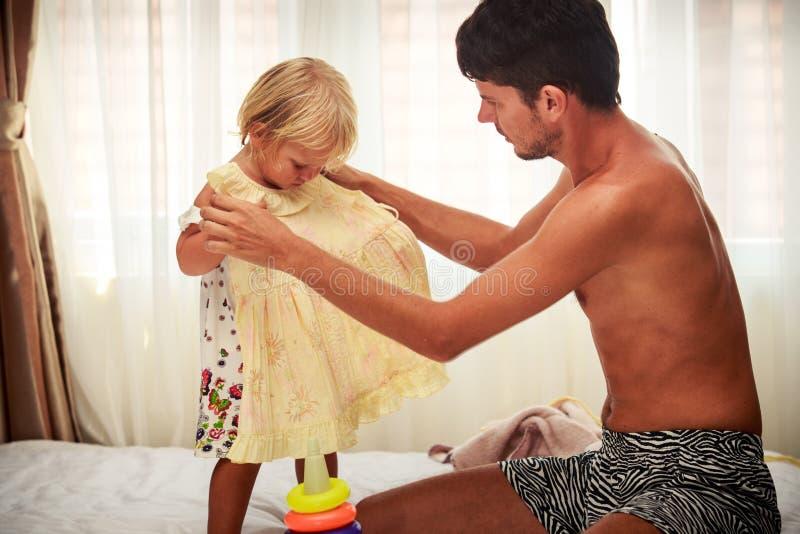 de vader wil poging op gele kleding aan dochter bij venster royalty-vrije stock fotografie