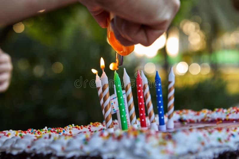 De vaderhand steekt kaarsen aan stock fotografie