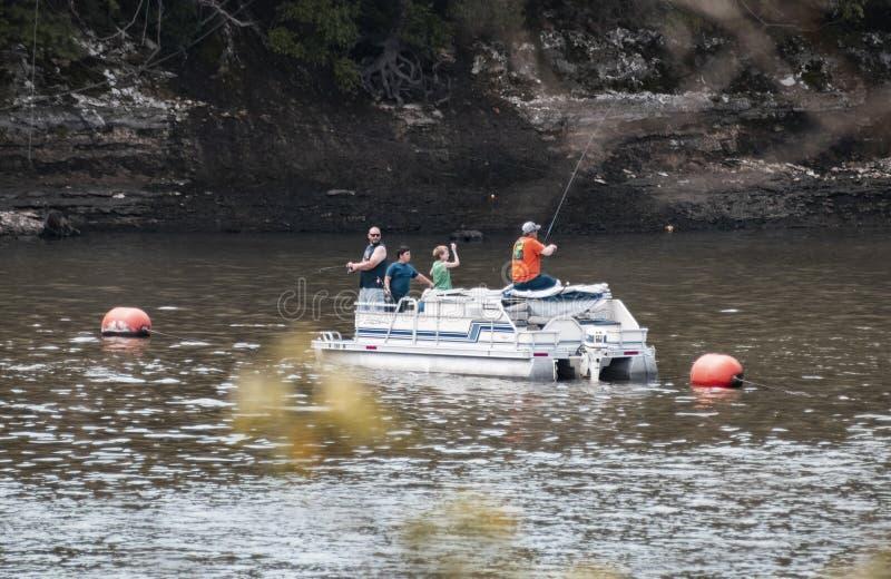 De vaders en de zonen uit in rivier op pontonboot die met rotsklippen erachter vissen en uit vaag gaan weg en vertakken zich het  royalty-vrije stock fotografie