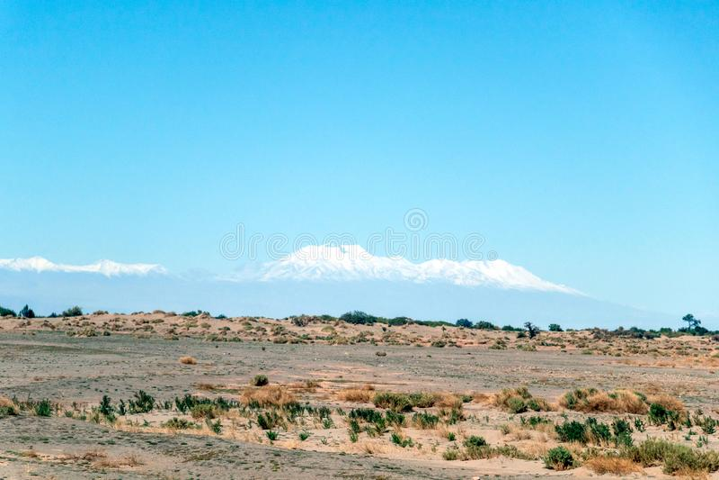 De vage achtergrond van Atacama-Woestijnlandschap met snow-capped Andesvulkanen, zout vlak en wat vegetatie op horizon, Chili stock foto's