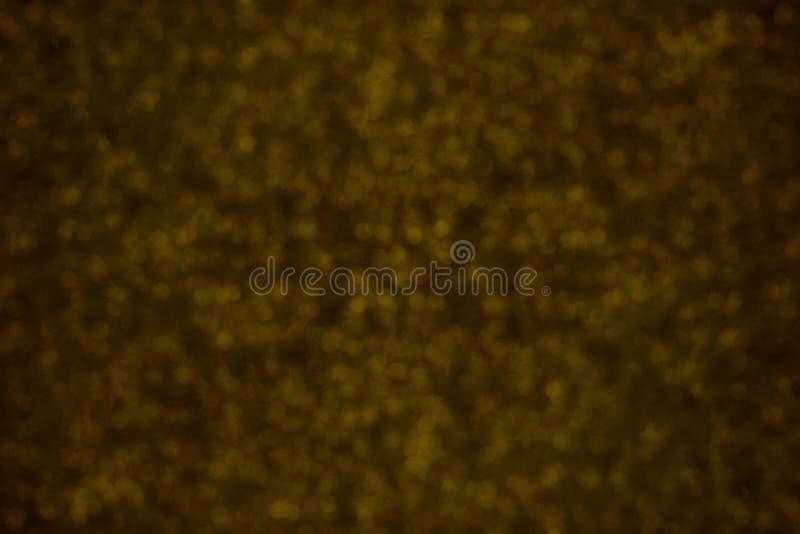 De vage glitterytextuur van schittert in geel op bruin Samenvatting stock fotografie