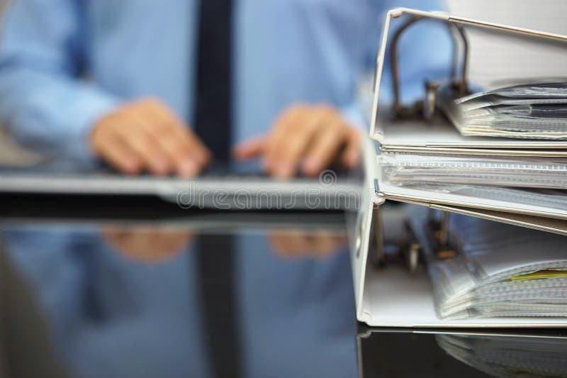 De vage zakenman typt op computertoetsenbord met documena stock foto