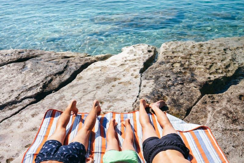 De vakantie ontspant: drie mensen nemen een zonbad na het zwemmen in c stock afbeelding
