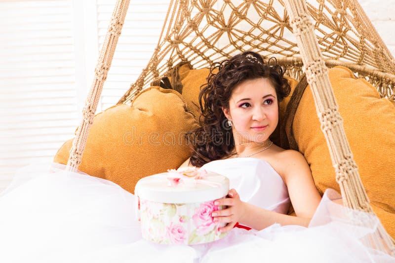 De vakantie, stellen, huwelijk en geluk het concept - glimlachende vrouw in witte de giftdoos van de kledingsholding voor royalty-vrije stock afbeeldingen