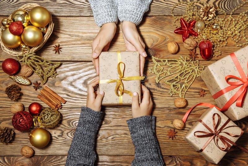 De vakantie, stelt, Kerstmis voor, kinderjaren en gelukconcept - sluit omhoog van kind en moederhanden met giftdoos stock afbeeldingen