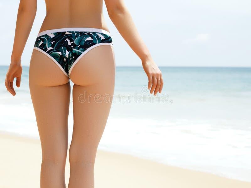 De vakantie van het strand Hete mooie vrouw in bikini status van strandoceaan op hete de zomerdag Sexy lichaam royalty-vrije stock afbeelding