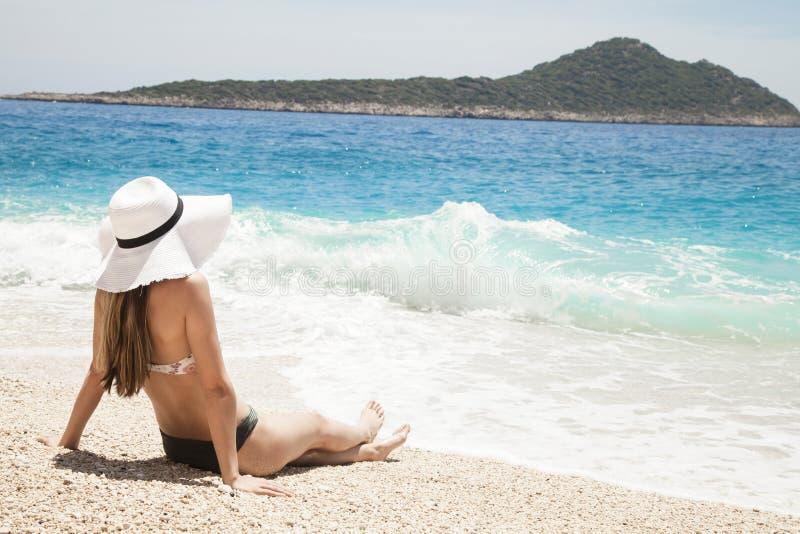 De vakantie van het strand Hete mooie vrouw in zonhoed en bikini die zich met haar die wapens bevinden aan haar het hoofd geniete royalty-vrije stock afbeeldingen