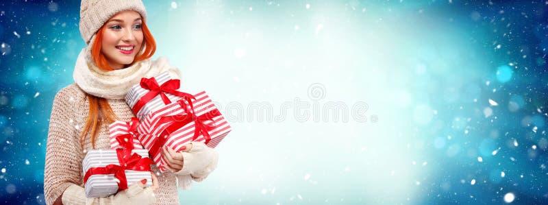 De vakantie van Kerstmis en van het Nieuwjaar Gelukkige readheadvrouw met giften Het winkelen de giftdozen van de vrouwenholding  stock foto's