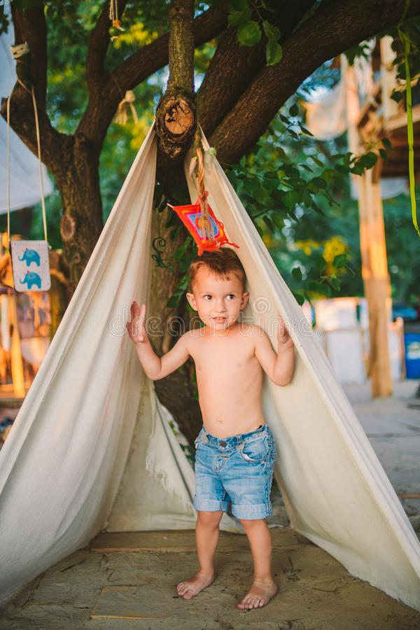 De vakantie van de themazomer, weinig jongen, het Kaukasische kind spelen op bebost gebied in park op speelplaats in de yard Het  royalty-vrije stock afbeelding