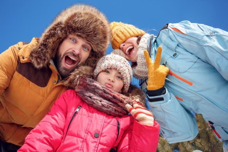 De vakantie van de winter Familietijd die samen in openlucht aan camera het lachen het speelse close-up van de bodemmening grimas stock fotografie