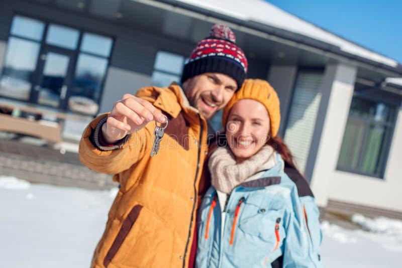De vakantie van de winter Jong paar die zich met sleutels van nieuw vage huisclose-up in openlucht verenigen die vrolijk glimlach royalty-vrije stock afbeelding