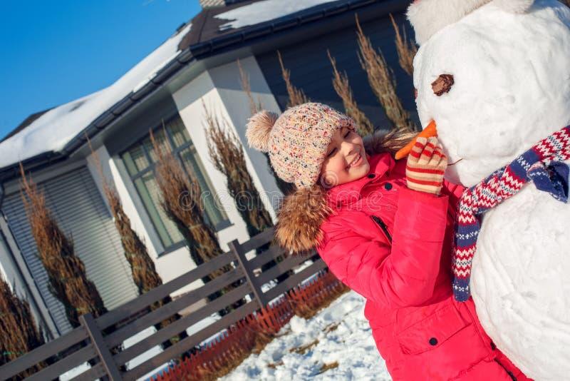 De vakantie van de winter Meisje die zich in openlucht dichtbij huis bevinden die sneeuwmanneus met wortel maken die gelukkig clo royalty-vrije stock foto's