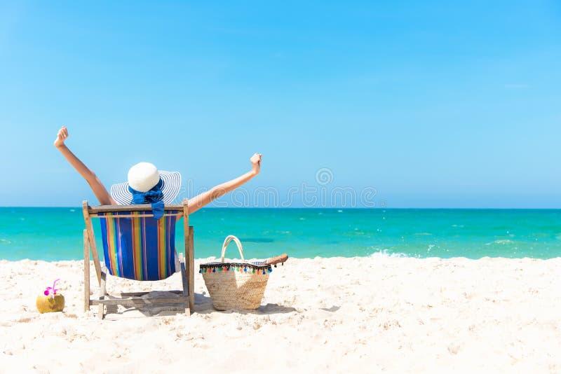 De vakantie van de zomer Mooie jonge Aziatische vrouw die en gelukkig op ligstoel met het sap van de cocktailkokosnoot ontspannen royalty-vrije stock foto's
