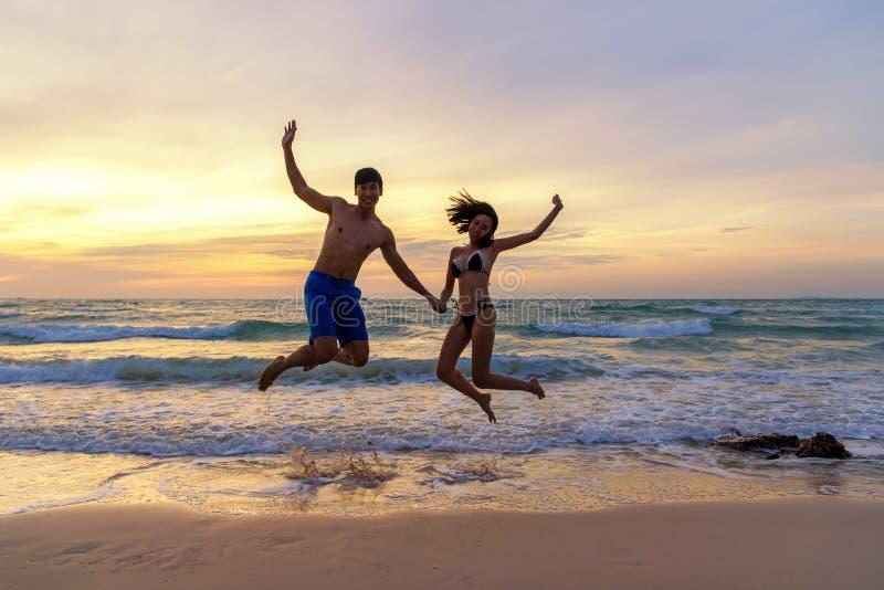 De vakantie van de zomer Paar het springen holdingshanden op tropisch op de tijd van de strandzonsondergang in vakantiereizen De  royalty-vrije stock foto's