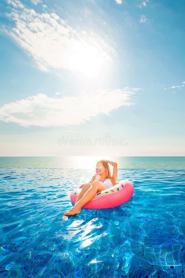 De vakantie van de zomer Vrouw in bikini op de opblaasbare doughnutmatras in het KUUROORD zwembad stock foto