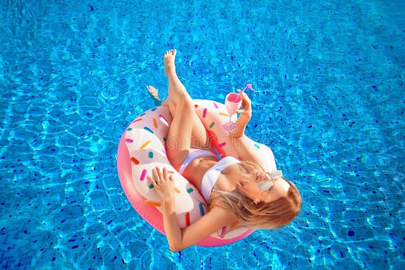 De vakantie van de zomer Vrouw in bikini op de opblaasbare doughnutmatras in het KUUROORD zwembad Reis naar de overzeese rest stock foto