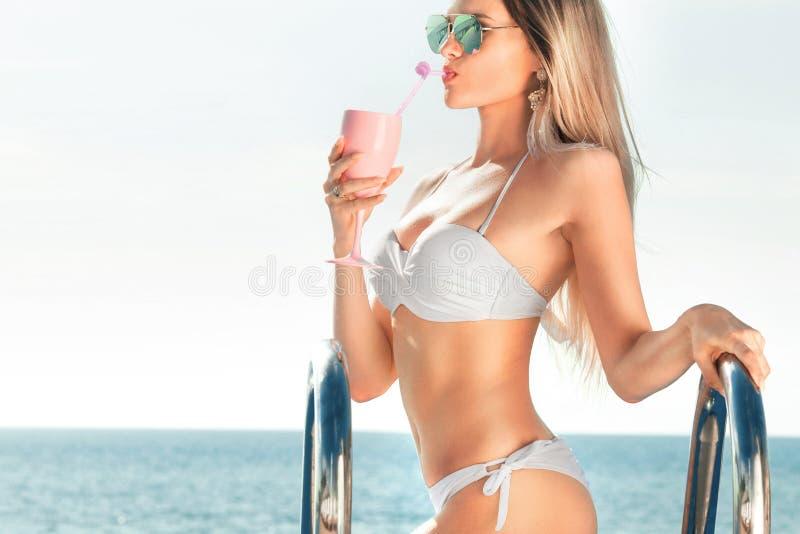De vakantie van de zomer Vrouw in bikini op de opblaasbare matras in het KUUROORD zwembad met coctail royalty-vrije stock afbeeldingen