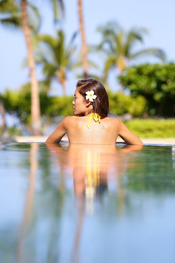 De vakantieconcept van de vakantie - vrouw het ontspannen in pool stock foto