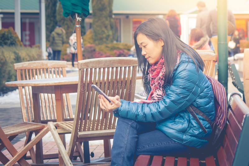 De vakantieconcept van de reiswinter: De Aziatische zitting van de vrouwenreiziger op houten lange bank bij buiten en het spelen  stock afbeelding