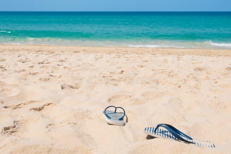 De vakantieconcept van de zomer Pantoffels op tropisch strand Zandig strand met overzees en blauwe hemelachtergrond royalty-vrije stock afbeeldingen