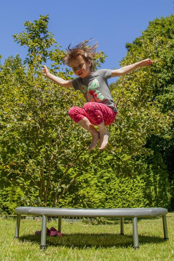 De vakantieconcept van de zomer Weinig zeer gelukkig leuk kindmeisje geniet van springend op trampoline royalty-vrije stock fotografie