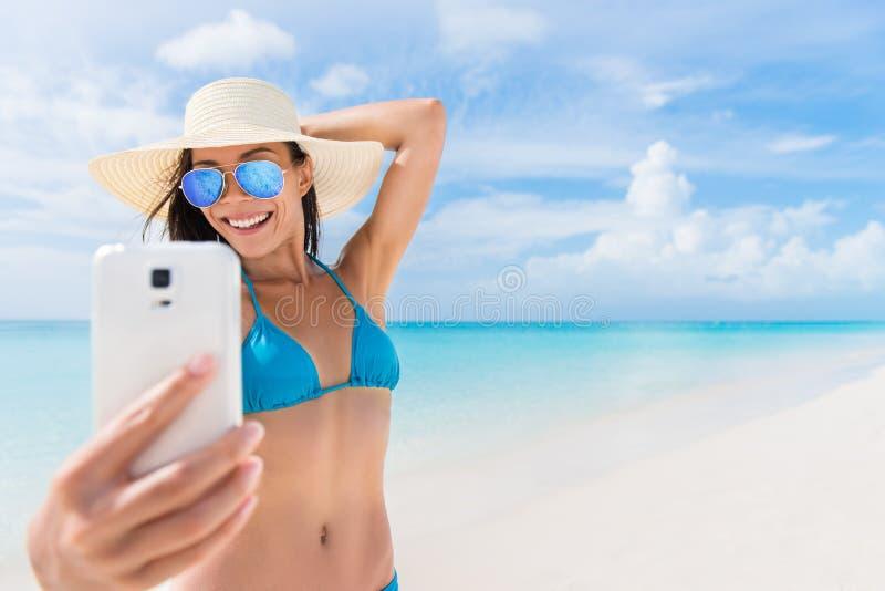 De vakantiemeisje die van het de zomerstrand prettelefoon nemen selfie stock afbeeldingen