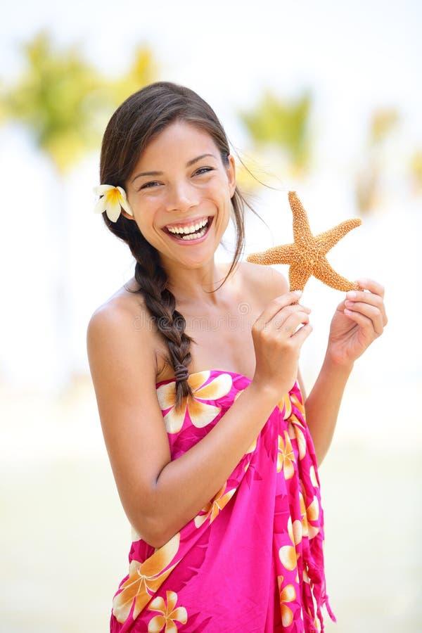 De vakantievrouw van de zomer glimlachen gelukkig met zeester royalty-vrije stock afbeeldingen