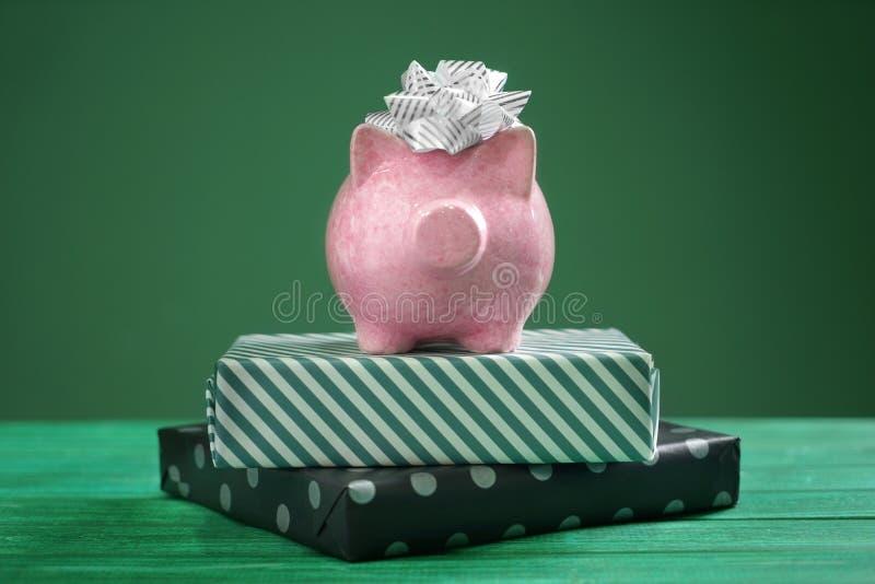 De vakjes van het spaarvarken en van de gift op kleuren houten lijst Concept besparingsgeld voor heden stock foto's
