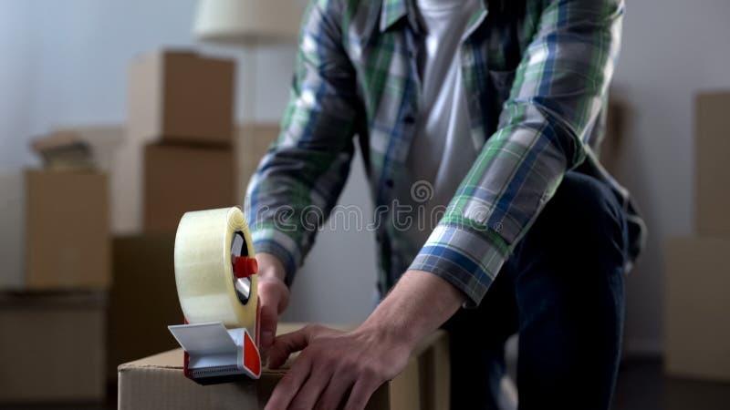 De vakjes van de jonge mensenverpakking met materiaal, die zich van flat, eind bewegen van huurcontract royalty-vrije stock afbeeldingen