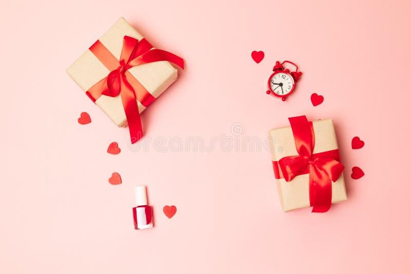 De vakjes van de verrassingsgift met rode booglinten, nagellak en rode klok op een roze achtergrond met plaats voor tekst stock afbeeldingen