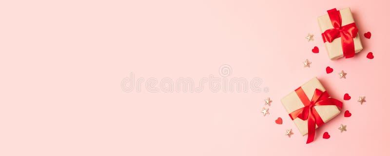 De vakjes van de verrassingsgift met rode booglinten, nagellak en rode klok op een roze achtergrond met plaats voor tekst stock fotografie