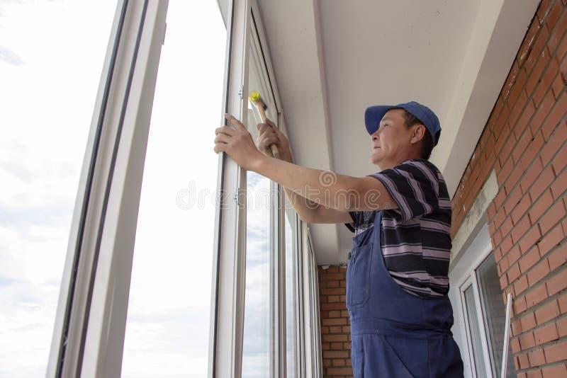 De vakliedenarbeiders installeren venster binnenshuis rammelen met een speciale rubberhamer stock fotografie