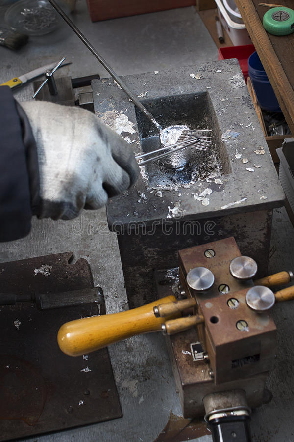 De vakman smelt oude naald in een ovengieterij uit royalty-vrije stock fotografie