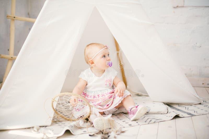 De vanger van de amuletdroom en weinig babymeisje één jaar met blauwe ogen, blonde zitten op de vloer in een kleding en houden stock afbeeldingen