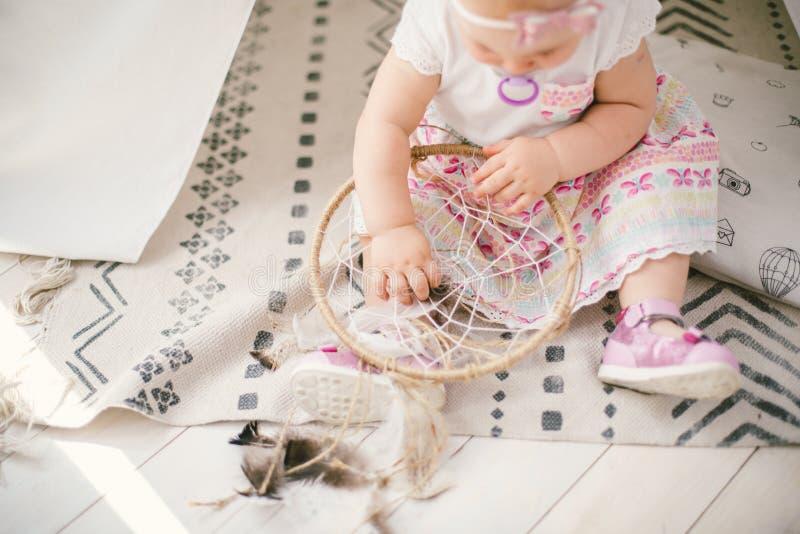 De vanger van de amuletdroom en weinig babymeisje één jaar met blauwe ogen, blonde zitten op de vloer in een kleding en houden stock foto