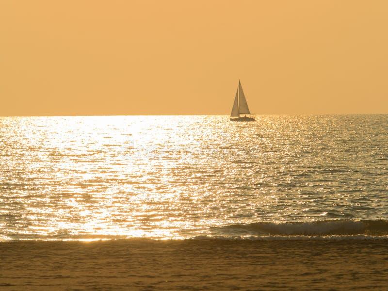 De varende die boot door zon wordt omringd schittert overzees op mooie zonsondergang stock afbeelding