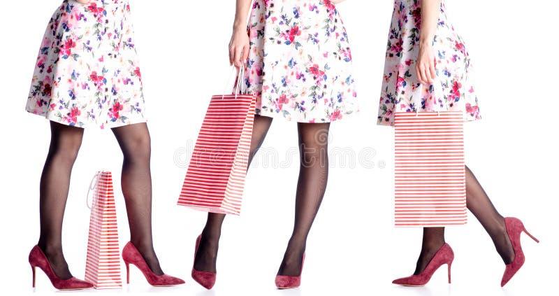 De vastgestelde vrouwenbenen in rode hoge hielschoenen en de kledingszak verpakken in hand manier stock afbeeldingen
