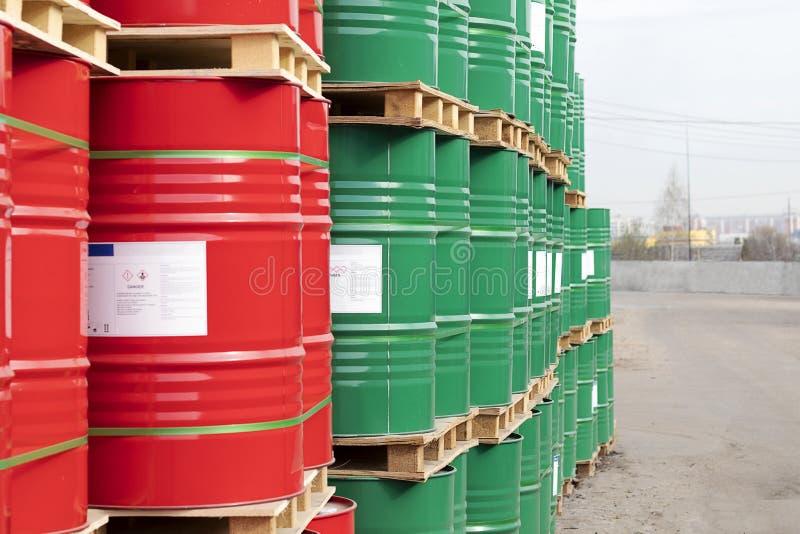 De vaten van 200 liter van metaal zijn in de pallet op de straat Rode en groene vaten voor aardolie, chemische producten, benzine royalty-vrije stock fotografie