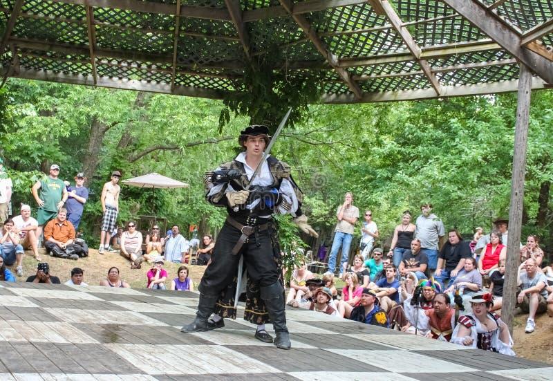 De vechter in middeleeuws kostuum kijkt verbaasd als vrouwenvechter speldt hem met zwaard van het Festival Mus van Renassiane van stock foto's