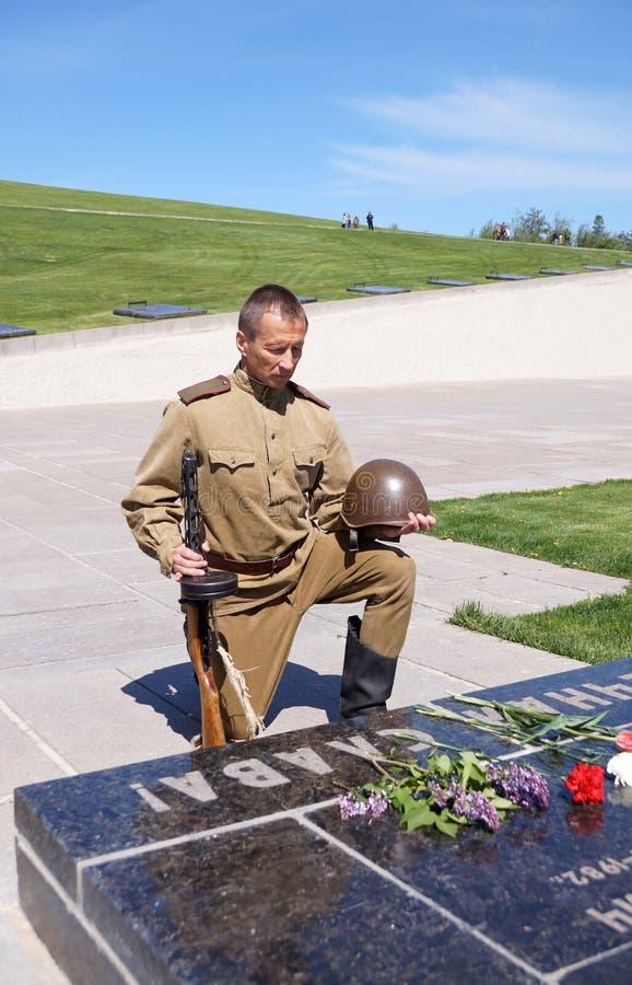 De vechter van Rood Leger boog een knie bij een grafzerk met een inscript stock afbeeldingen