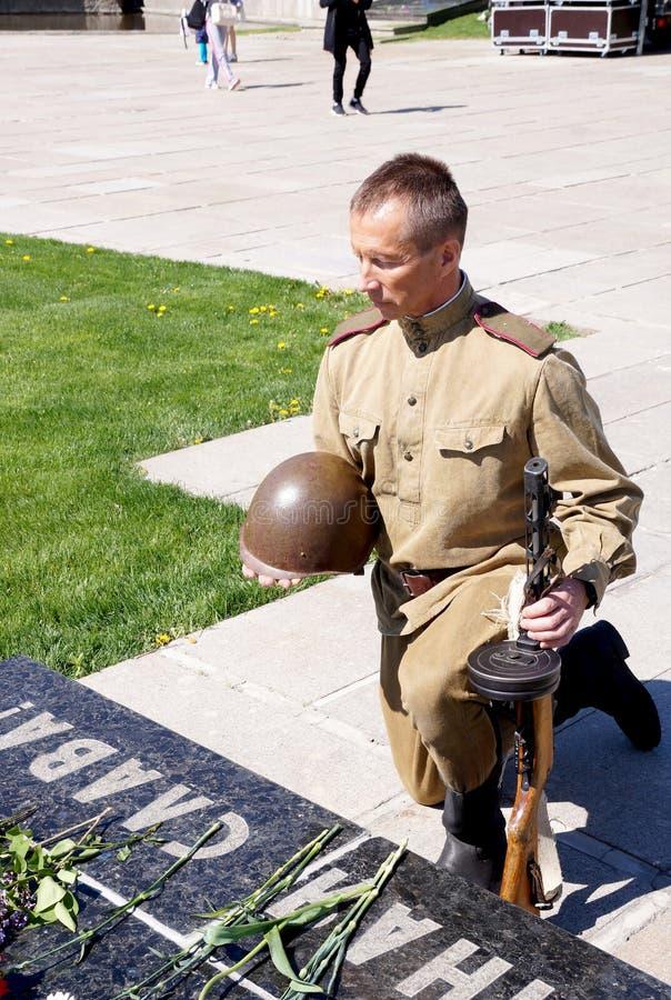 De vechter van Rood Leger boog een knie bij een grafzerk met een inscript stock fotografie