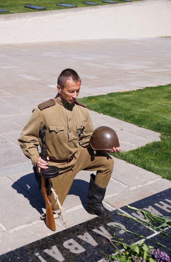 De vechter van Rood Leger boog een knie bij een historisch monument in memorandum stock foto's