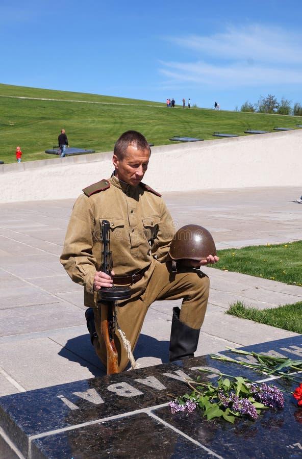 De vechter van Rood Leger boog een knie bij een historisch monument in memorandum stock afbeeldingen
