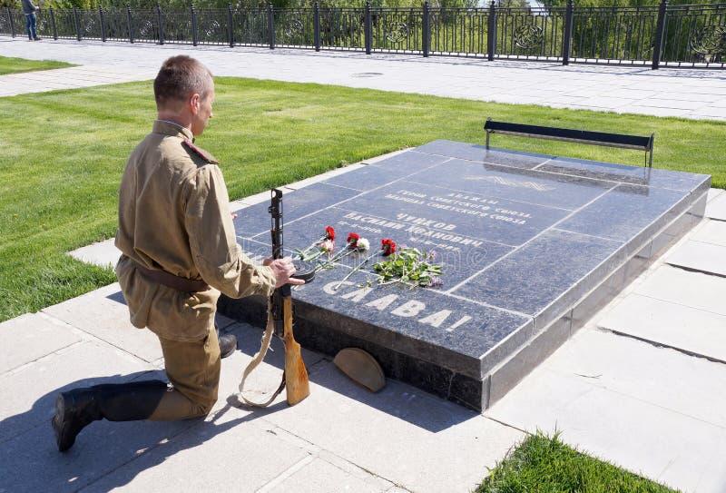De vechter van Rood Leger boog geknield bij het graf van Hofmaarschalk Chuikov royalty-vrije stock afbeeldingen