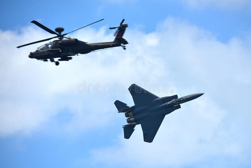 De vechtersstraal van RSAF F-15SG en Apache-helikopter die kunstvliegen uitvoeren in Singapore Airshow stock afbeeldingen