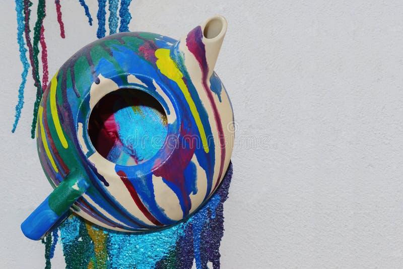 De veelkleurige geschilderde theepot is in bijlage op de verticale muur met exemplaarruimte royalty-vrije stock afbeelding
