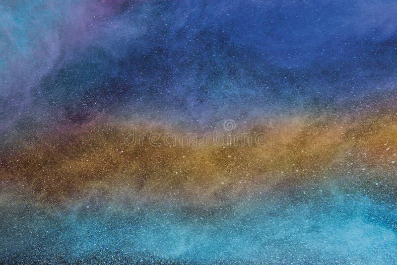 De veelkleurige mist, de mist, de rook of het poeder zijn vlieg uitgespreid hoogtepunt in ruimte stock foto