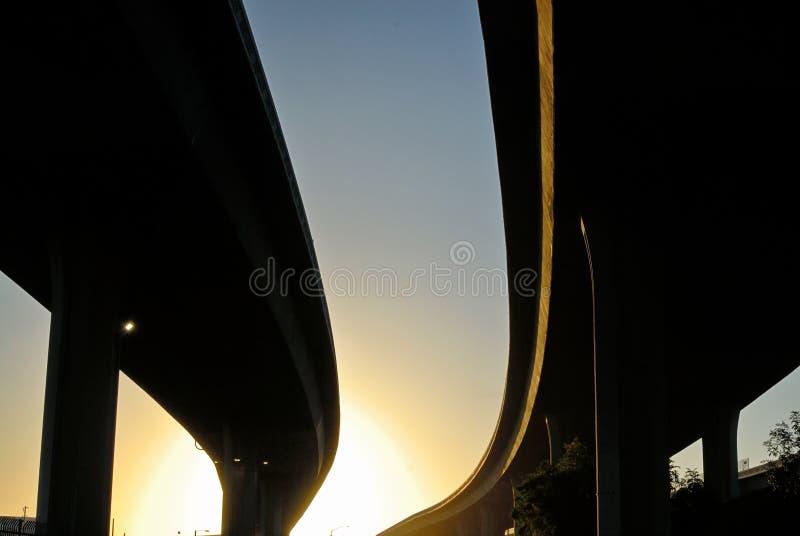 De vegende stotende silhouetten van snelweguitwisselingen stock afbeeldingen